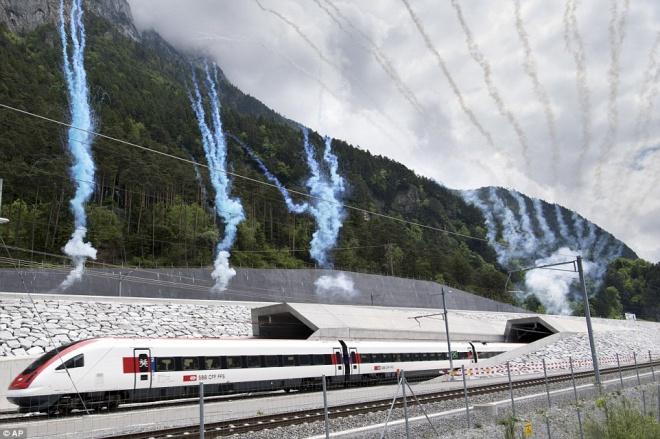 Félmeztelen táncosok a világ leghosszabb vasúti alagútjának bizarr átadóünnepségén!